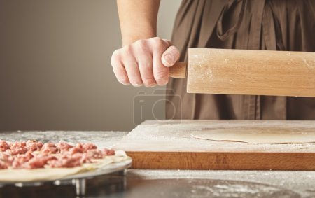 Flatten dough with wooden rolling pin