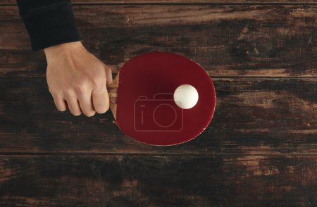 Hand holds professional wooden ping pong rocket above table