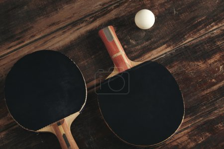 Two professional ping pont rockets on antique wooden table isola