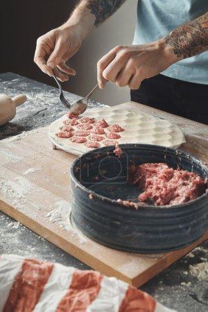 man cooks pelmeni or dumplings or ravioli in special mold