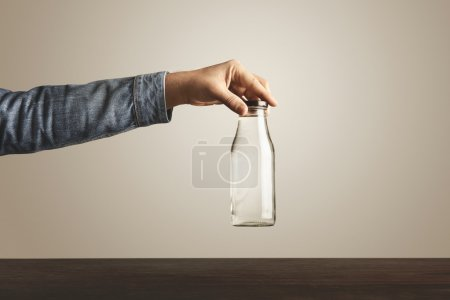 Brutal hand holds glass bottle with water