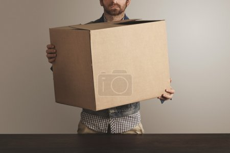 Photo for Bearded brutal courier in jeans work jacket holds big carton paper box with goods above wooden table. Special delivery, retail shipping post box - Royalty Free Image