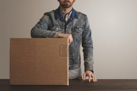 Photo for Bearded brutal courier in jeans work jacket stays near presented big carton paper box with goods on wooden table. Special delivery, retail shipping post box - Royalty Free Image
