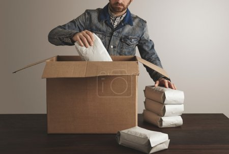 man puts packages inside carton box