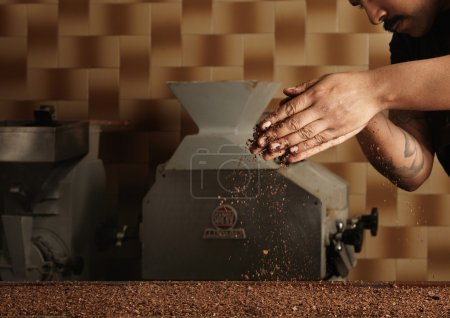 Baker pours grained nuts on chocolate mass