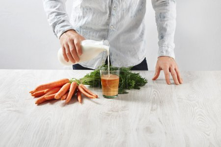 man pours milk to glass with carrot juice
