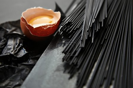 Photo pour Gros plan se concentrer sur les spaghettis noirs sur le bureau en marbre noir et le papier d'artisanat près de l'œuf cru cassé avec le jaune à l'intérieur. Riche texture de luxe - image libre de droit