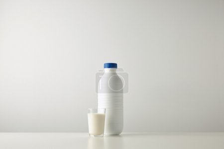 Plastic white bottle near glass with milk