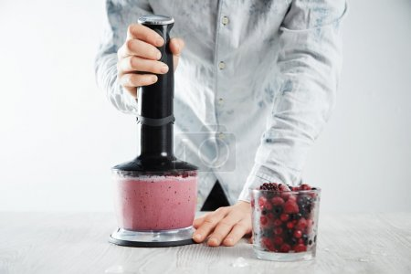 Man blends frozen berries, ice, yogurt