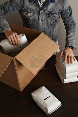 man puts hermetic packages inside big carton box