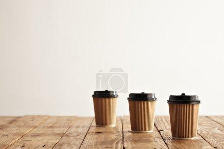 Three carton paper cups in row
