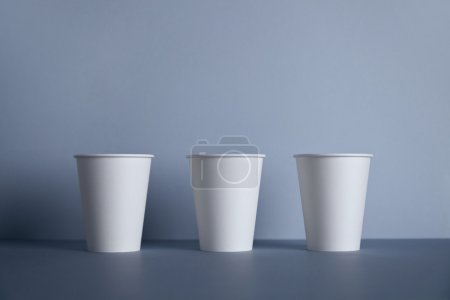 Three white paper cups in row