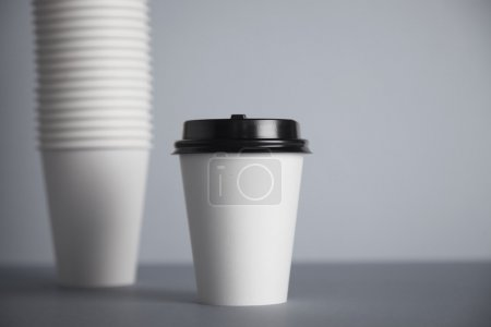 Photo for One focused take away white paper cup with black cap presented in front of unfocused group of other cups folded one in other in big bunch, isolated on simple gray background - Royalty Free Image