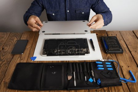 Photo for Service man opens backside top-case cover of computer laptop before repairing, cleaning and fixing it with his professional tools from toolkit box near on wooden table front view - Royalty Free Image
