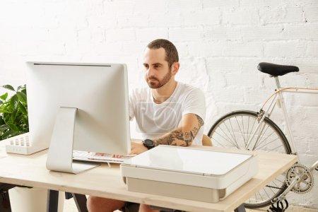 Photo pour Jeune homme indépendant tatoué attrayant en t-shirt blanc vierge travaille sur son ordinateur à la maison près de son vélo, à la recherche dans l'affichage - image libre de droit
