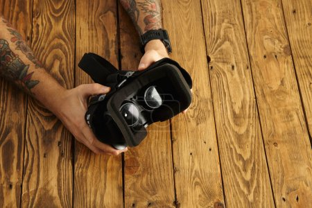 Tattoed hands hold vr glasses