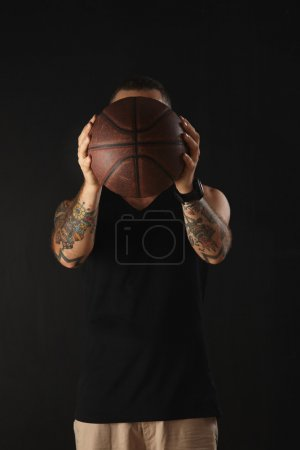 athlete with tattooed hands holds ball