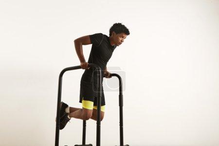 black athlete doing dips on parallel bars