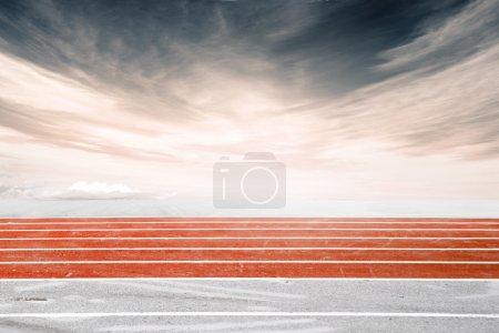 Photo pour Un plan latéral d'une belle piste de course orange sur le fond d'un ciel nuageux foncé gris rougeâtre. Image commerciale - image libre de droit