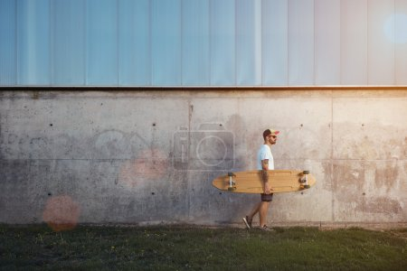 Tattooed man carrying a longboard