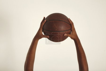 Two hands hold vintage basketball