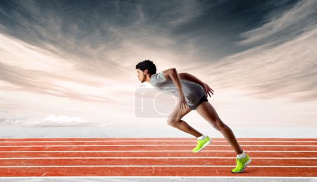 Photo for Side shot of a muscular latin runner learing strongly forward on orange track against dramatic sunset sky background - Royalty Free Image