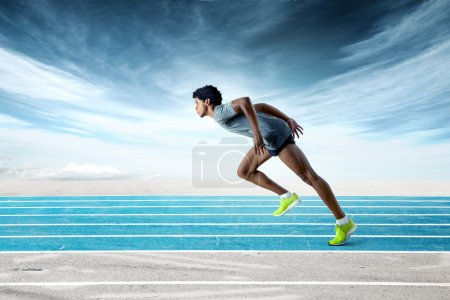 Photo for Portrait of a fit black runner wearing gray shirt, black shorts and neon green sneakers on blue track against dramatic sky background - Royalty Free Image