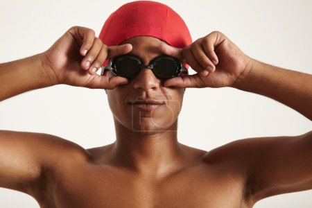 swimmer in red cap putting on black goggles