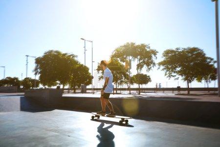 longboarder in a sunlit skate park skating away