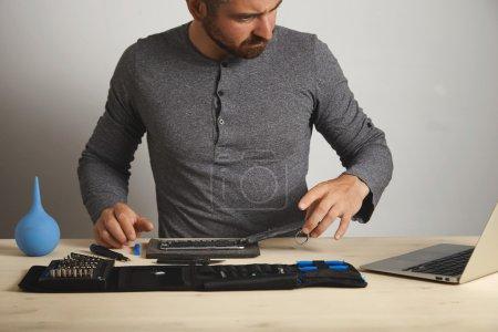 Photo pour Homme à la recherche dans l'ordinateur portable et il suit pour réparer son smartphone cassé, boîte à outils avec des outils spécifiques près - image libre de droit