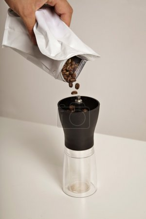Coffee beans fall into manual grinder