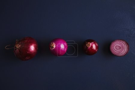 Four red various onions: normal, peeled, partially peeled and splitted