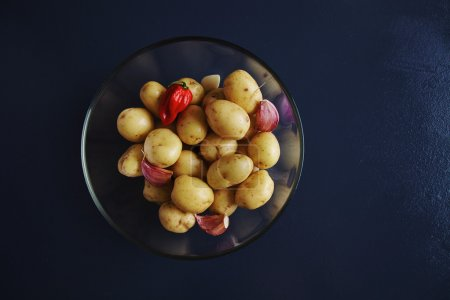 Baby potatoes with garlic and hot red pepper in transparent bowl