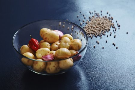 Baby potatoes with garlic in transparent bowl