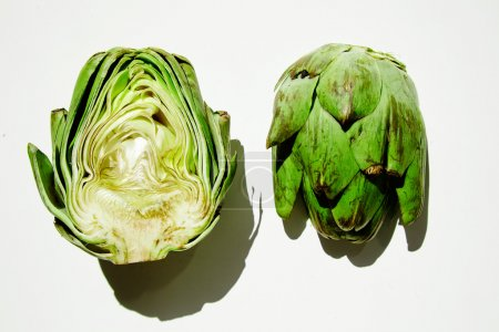Artichoke half split on white table direct sunlight shadows