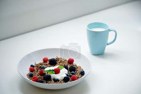Breakfast with glass of mik and integral musli with berries mix