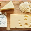 Four cheeses closeup on wooden board...
