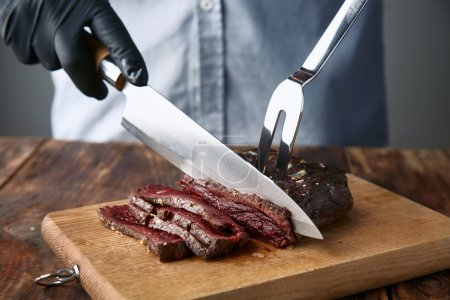 Hands in black gloves slice medium rare cooked whale meat steak