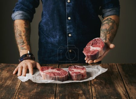 butcher with tattooed hands offers raw meat steak