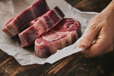 Closeup hand holds white paper three raw steaks