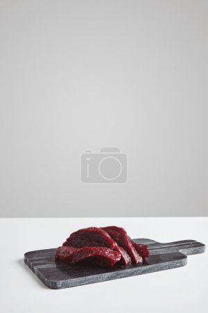 Sliced whale meat steak on marble board isolated