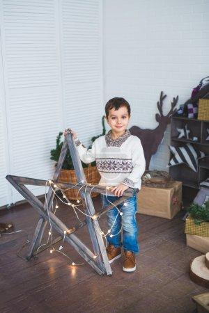 A Cute boy stands near a wooden star in a studio
