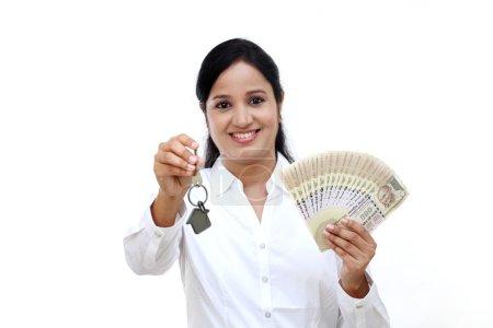 Photo pour Femme d'affaires détenant la clé de la maison et de billets de banque Indiens - image libre de droit