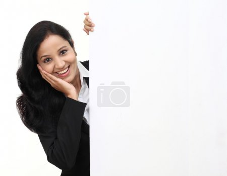 Young cheerful business woman showing a blank sign board