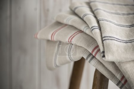 Stack of Striped Linen on a Wooden Stool