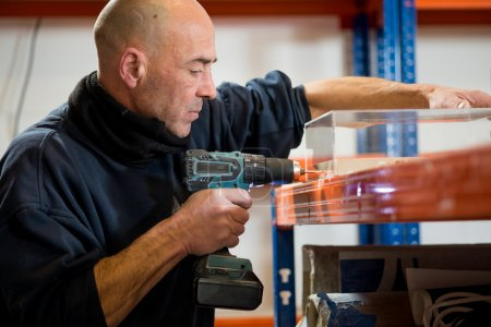 Man with Power Drill Punching Hole on a Clear Plastic Case