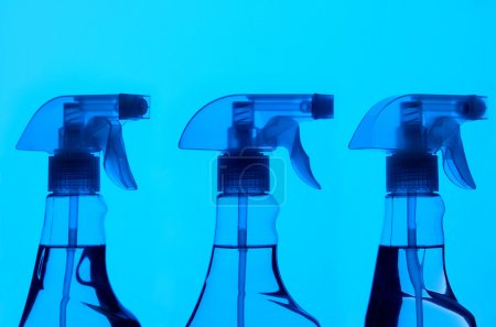 Three Spray Bottles With Blue Light