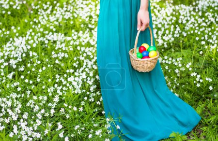Basket of easter eggs on meadow