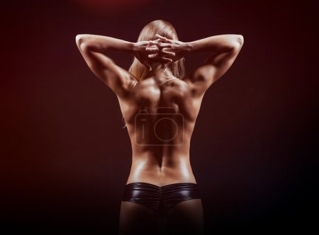 Muscular fitness woman posing on a dark background