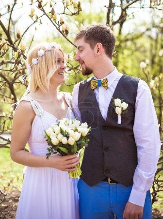 Photo pour Mariée heureuse et marié posant au parc près de fleurs de printemps le jour du mariage - image libre de droit